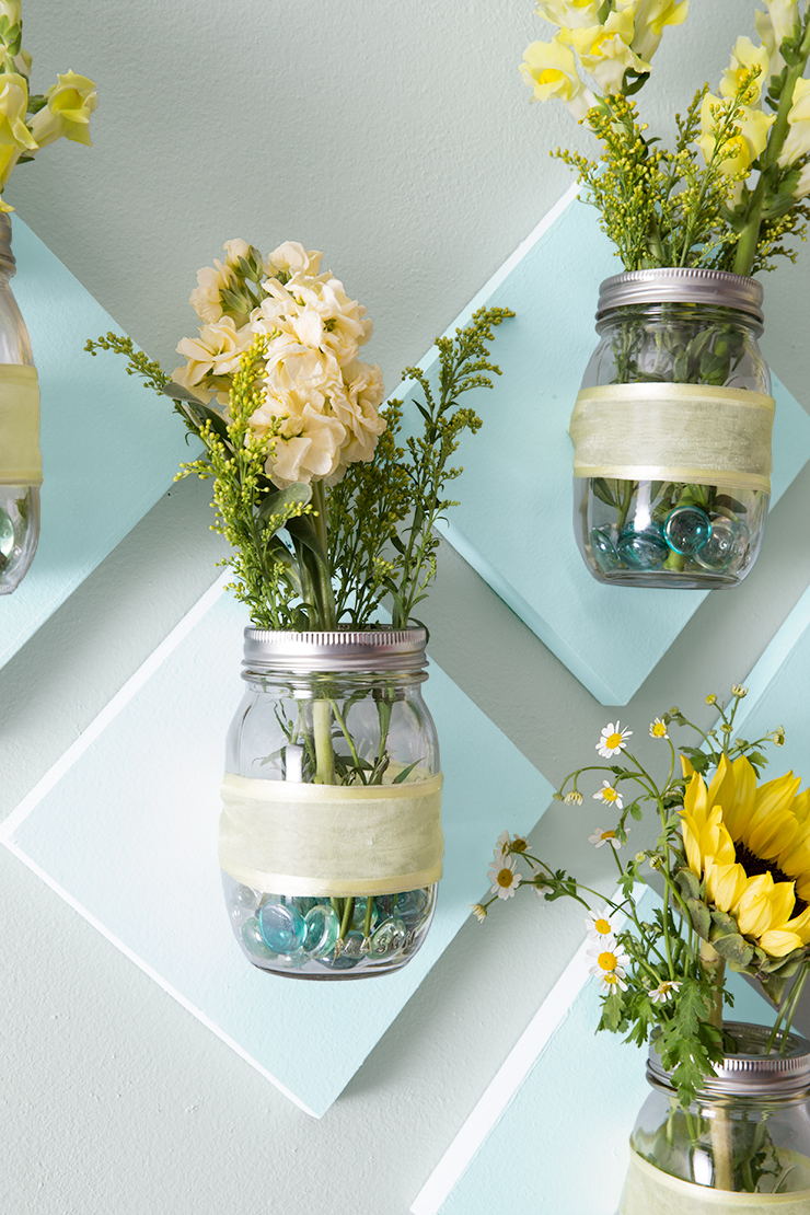 Mason jar flower display on wall zoomed in.