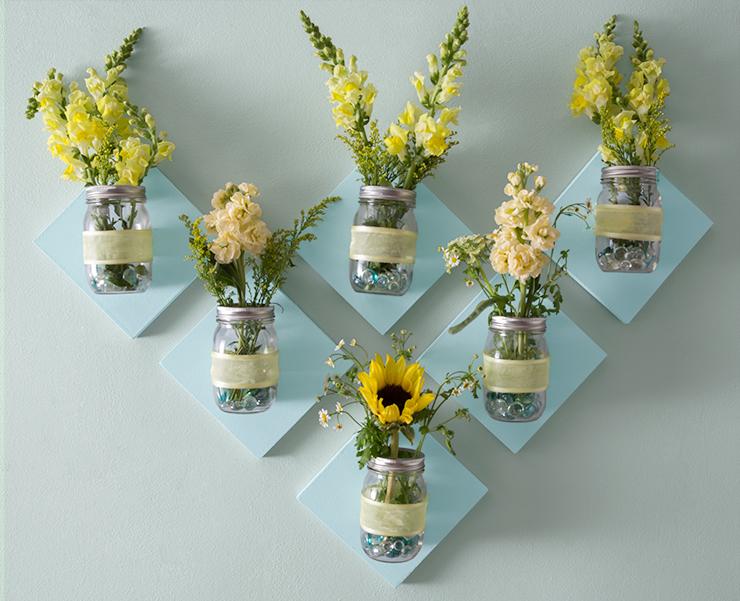 Mason jar flower display on wall.