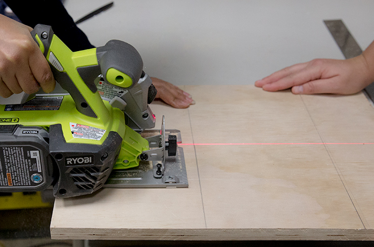 cutting the board with a handsaw