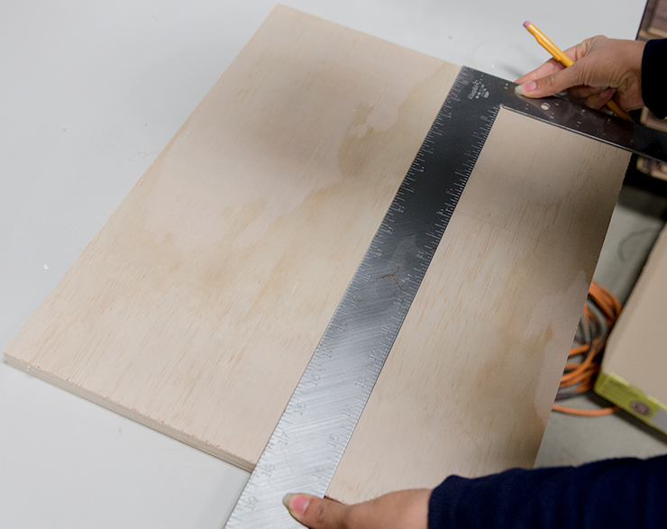 Woman's hands taking measurements of the wood board.