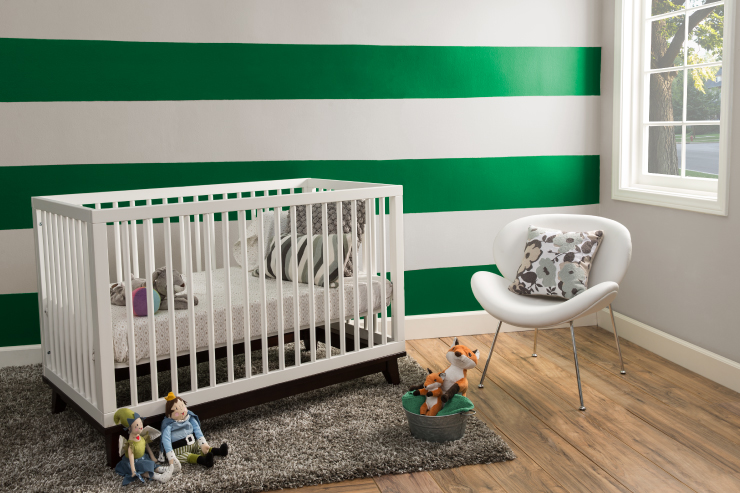 A nursery with white furniture. The wall is painted in green and white stripes.