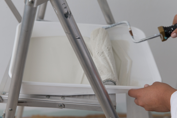 Paint tray with white paint sitting on a ladder.