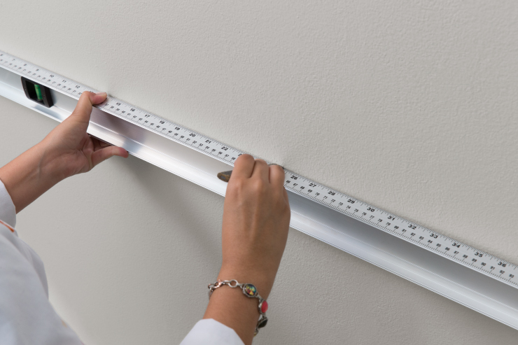 using a leveler tool against the wall.