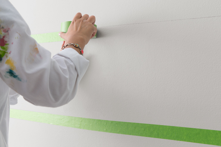 Adding green masking tape to the wall using the pencil marks as a guide.