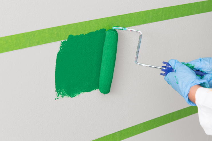 Painting green onto the wall within the masking taped area.