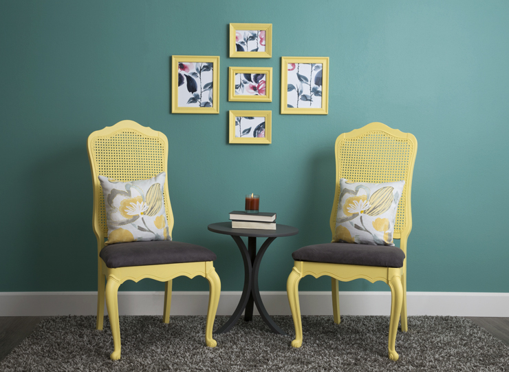 Sitting area with two yellow chairs. The wall behind them is painted in an aqua color.