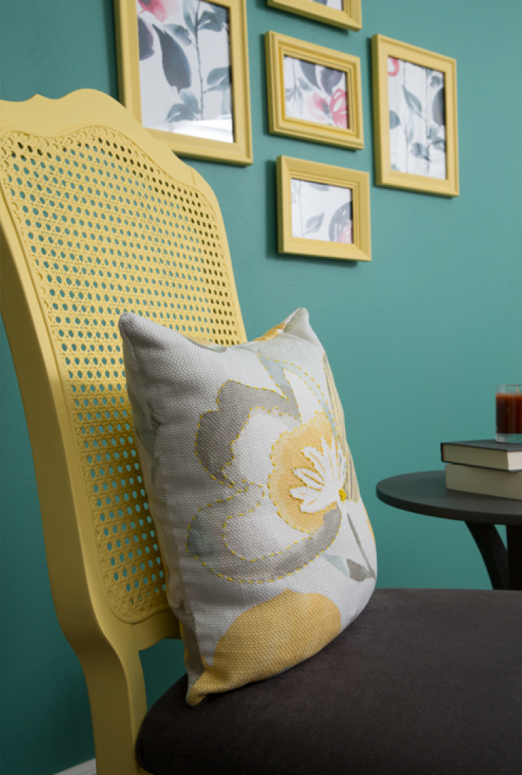 A close up view of the chair with a yellow and gray pillow sitting on it.
