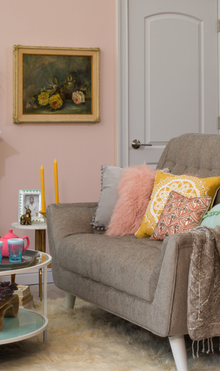 A living room with pillow in yellow. Walls are pink and  door is gray.