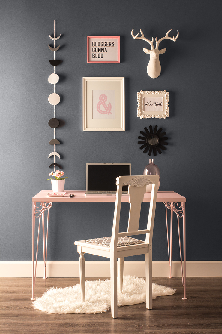 A small office area with a pink desk and white chair. Walls in room are gray. On the wall is art in white and pink frames and a moon phase mobile.