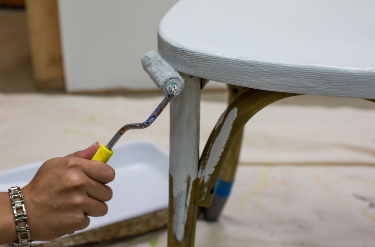 painting the chair leg with white paint.