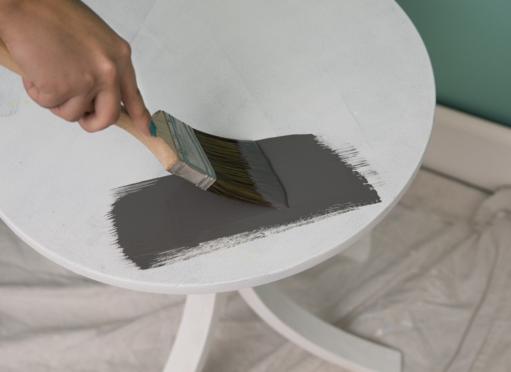 A person painting a white table the color gray.