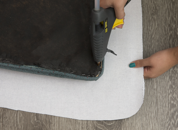 Adding glue with a hot glue gun to the cushion.