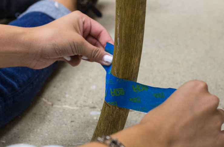 Adding blue masking tape to a chair leg.