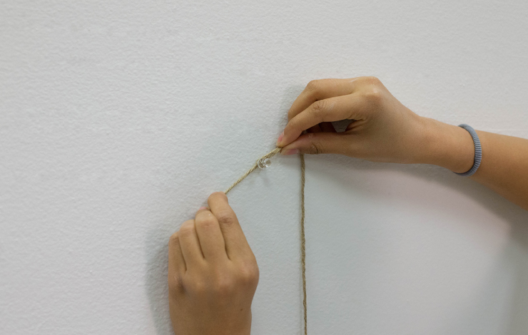 Add tack to wall and tie rope around tack.
