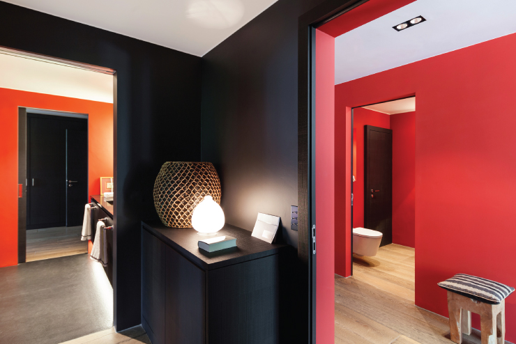 A hallway area that peaks into two other rooms. The rooms are painted in bold colors.