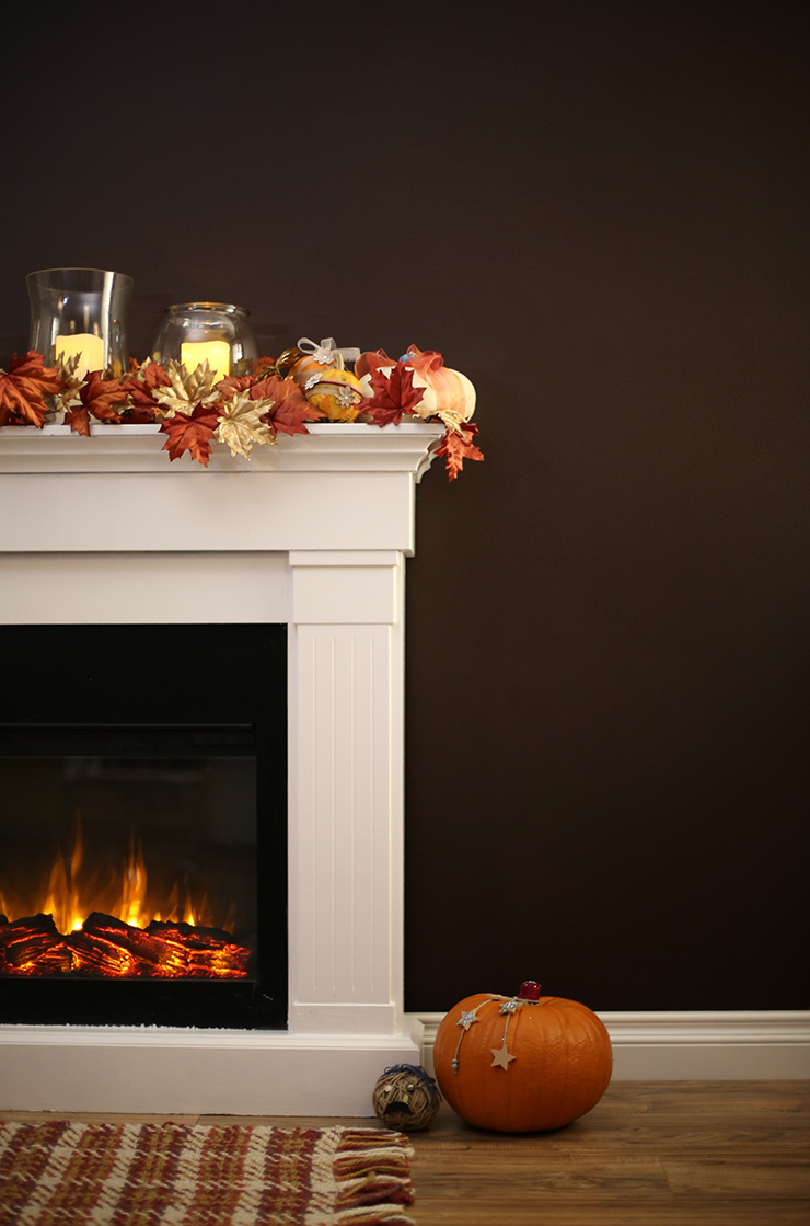 A lit fireplace with the mantel decorated with fall leaves, candles and pumpkin.