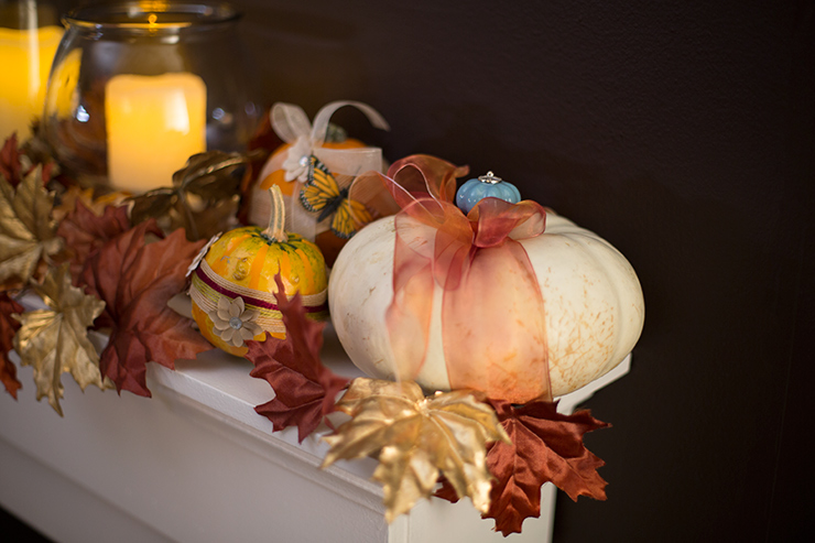 A close-up top view of a mantel decorated with fall leaves, candles and pumpkin.