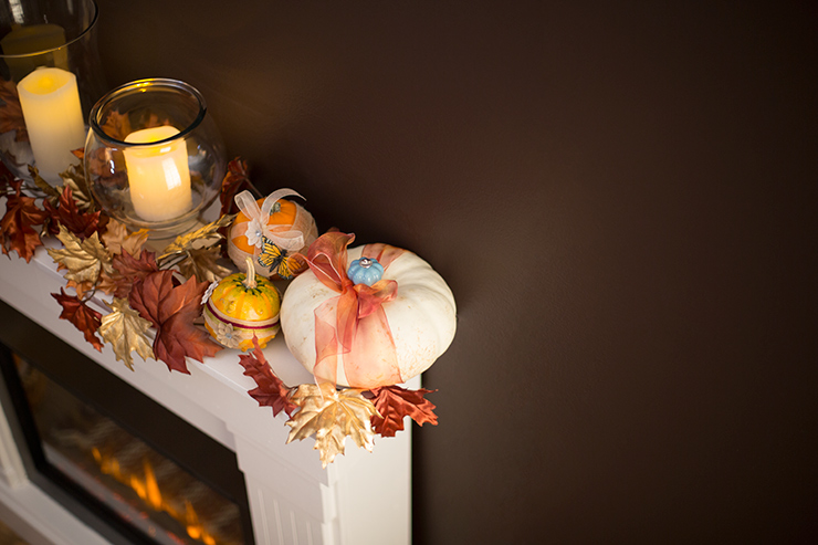 A top view of a lit fireplace with the mantel decorated with fall leaves, candles and pumpkin.