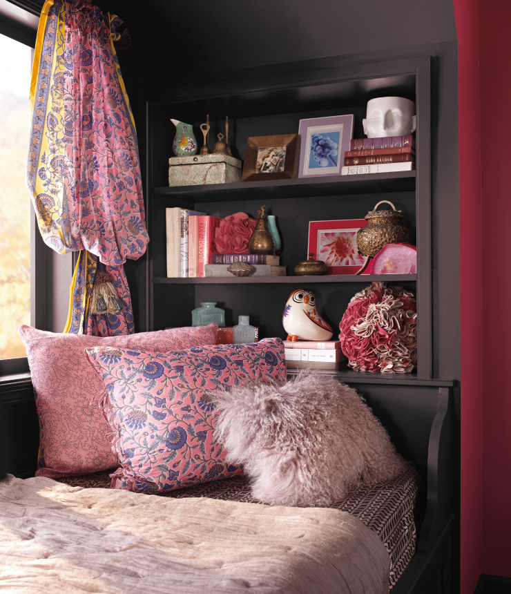 A bedroom decorated with pink and red accents. The wall is painted in Black Garnet.