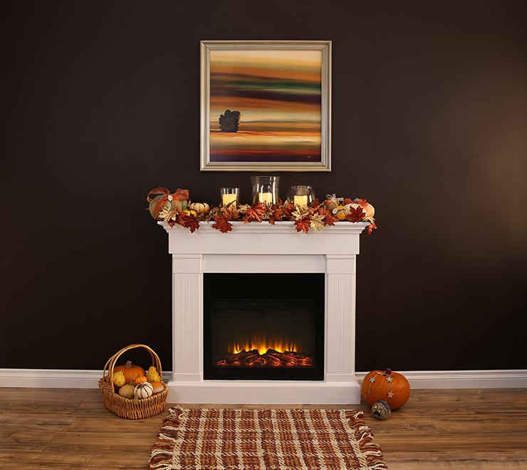 A room with a  lit fireplace with the mantel decorated with fall leaves, candles and pumpkin.