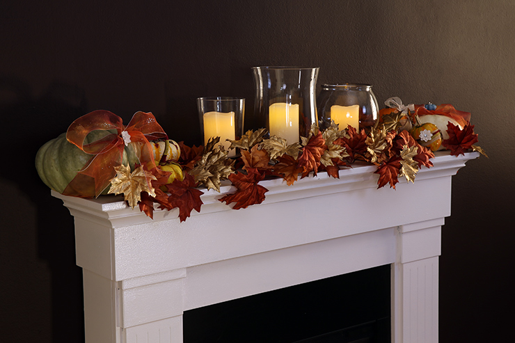 A mantel decorated with fall leaves, candles and pumpkin.