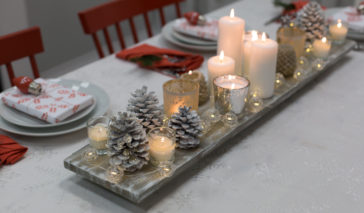 Table runner board centerpiece decorated with lit candles and painted pine cones sitting on a distressed wood plank.