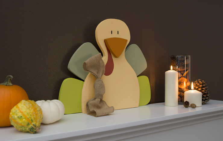 Mantel decorated with a wood painted turkey.