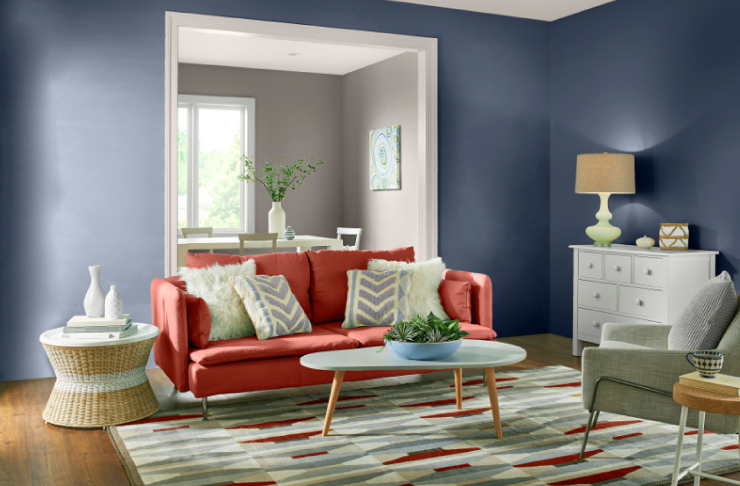 A living room with blue walls and accents in red.