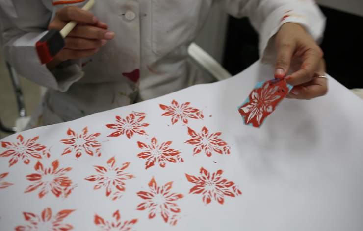 Painting with stencil on white wrapping paper.