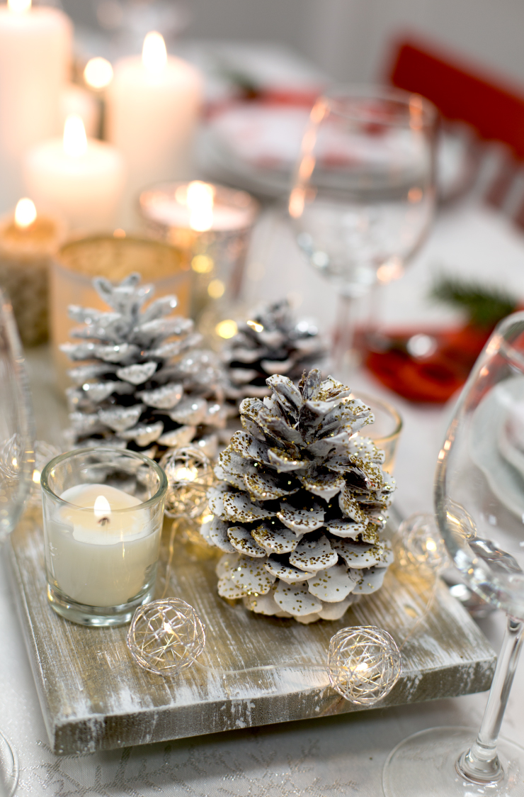 Glitter pinecones and lit gold string lights placed on a table.