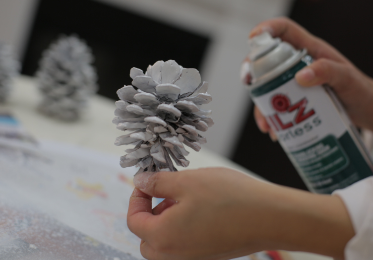 Woman's hands spraying painting a pine cone with primer coat.