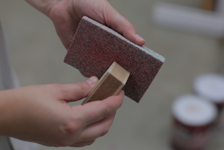 Person using a sand block to smooth edge of wood block.