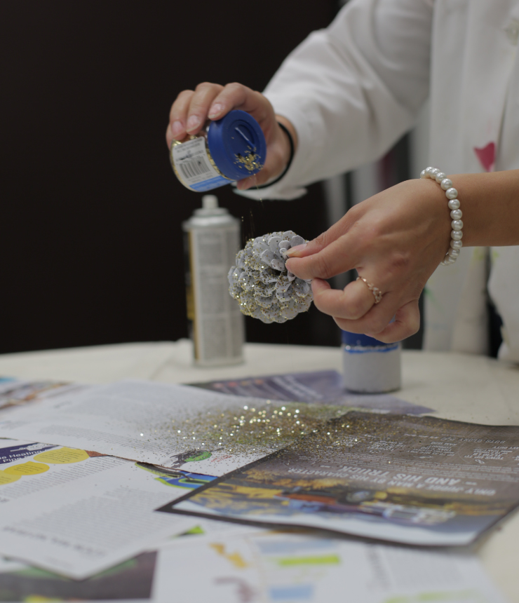 Adding glitter to pinecone.