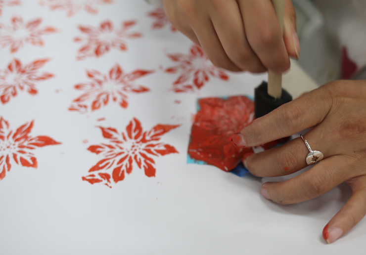 Painting a poinsettia pattern using a sponge brush and a stencil.