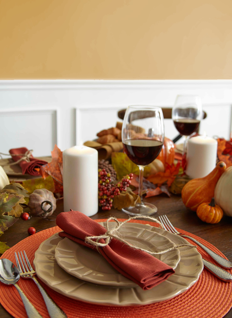 Close up of a table showing a place setting in fall decor with wall in background painted in Gold Hearted.