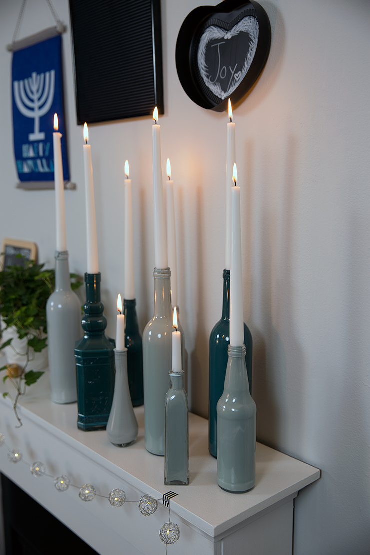 Painted jars with lit candles inside placed on mantel.