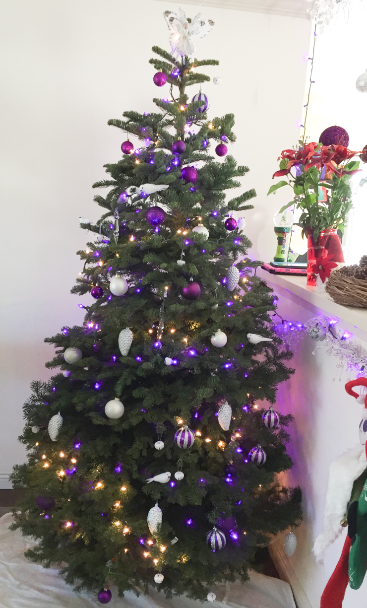 A holiday tree decorated with white doves, purple lights and bulbs colored in purple and white.