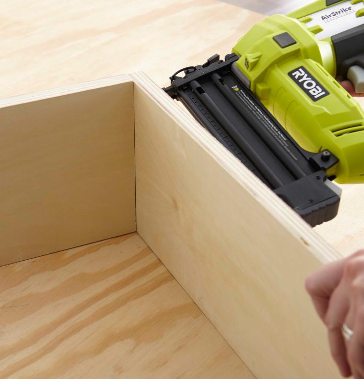 Using a nail gun to nail crates together.