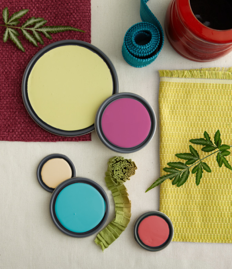 A color palette of yellows, coral, pinks and green created with paint lids and material.