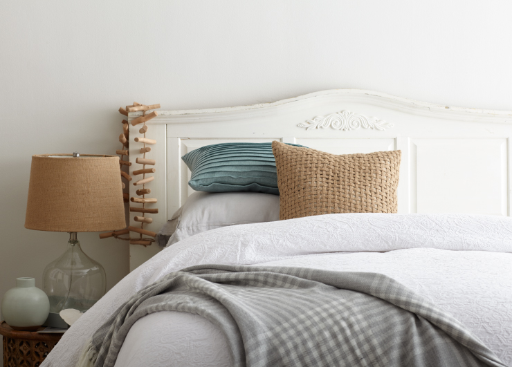 Bedroom with white walls. The bedding is styled with white and grays and a pop of a light blue.