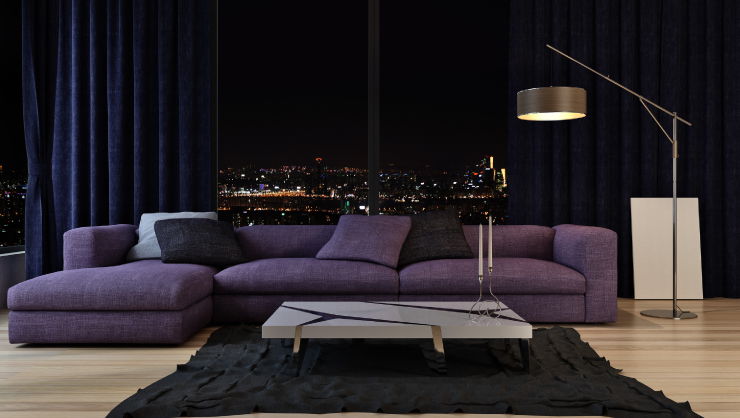 A living room with a deep-purple colored couch.