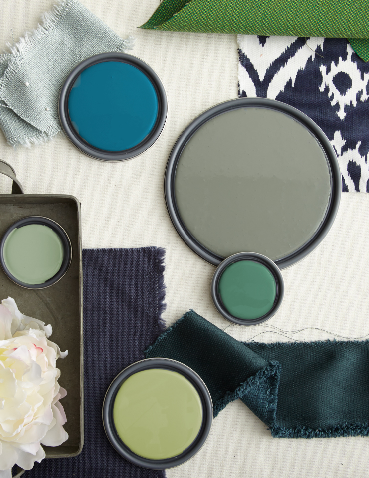 A color palette of greens, blues and yellows created with paint lids and material.
