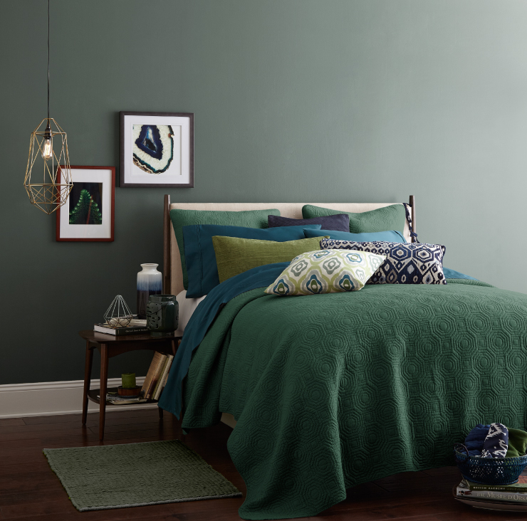 Bedroom with green wall and blue, purple, and yellow pillows.