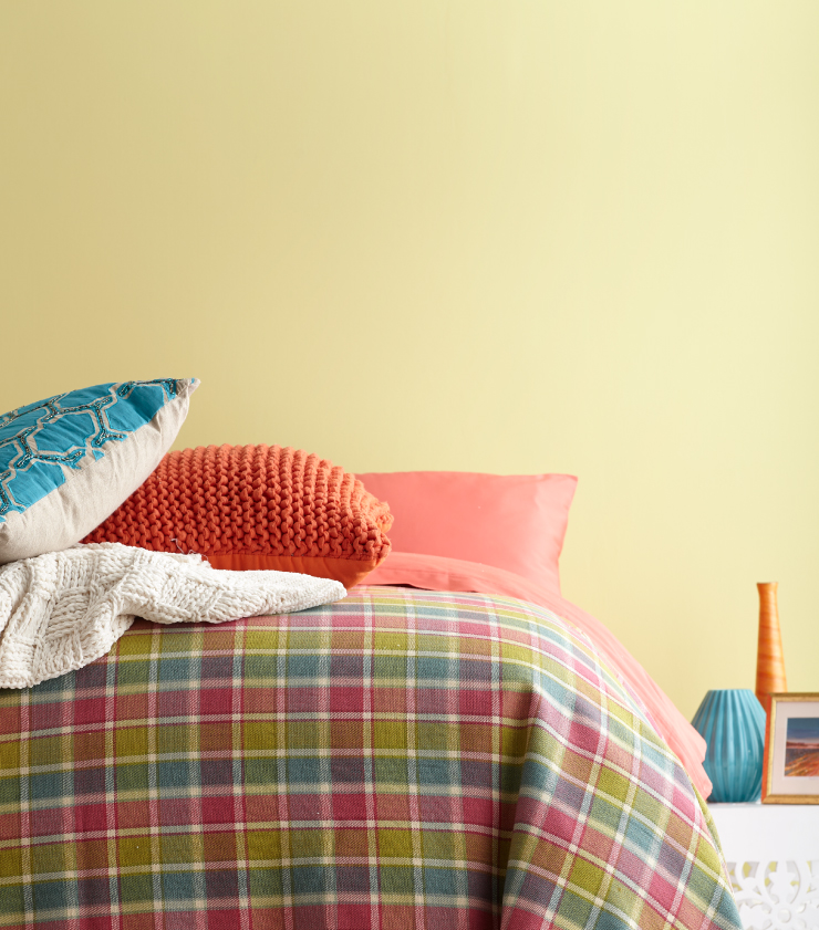 A bedroom with yellow walls. The bedding is coral, yellow and green.