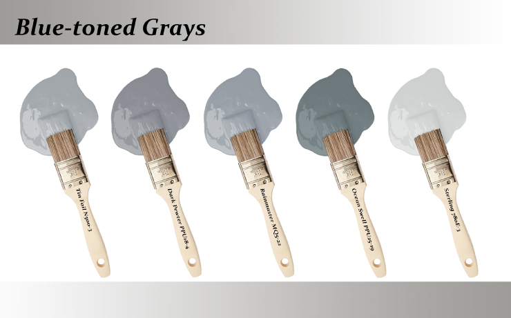 Five paint brushes dipped into paint drops that are Blue-toned grays colors.