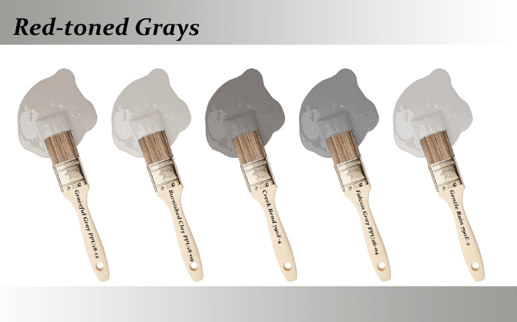 Five paint brushes dipped into paint drops that are red-toned grays colors.