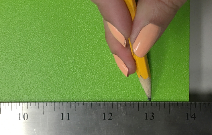 Ruler and pencil marking a spot on the green board.