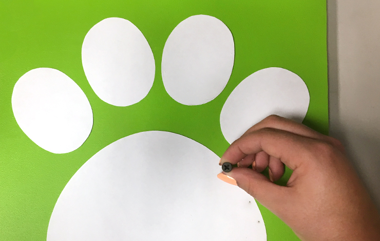 A person using a screw to mark holes along the paw print.