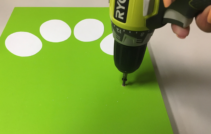 A person drilling holes into the green board.