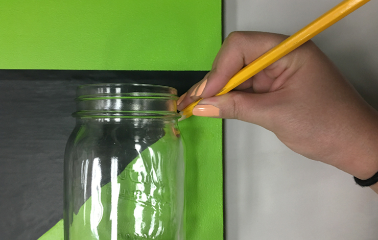 Glass mason jar placed in front of board and person marking height with a pencil.